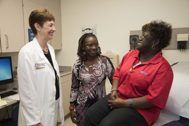 Laura Jean Bierut, MD (left), and Foluso Ademuyiwa, MD (center), discuss genetic risks for breast cancer with patient Delores Ford-Dixon. Robert J. Boston photograph